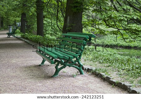 An empty green bench in the park in Uman Sophia, Ukraine - stock photo