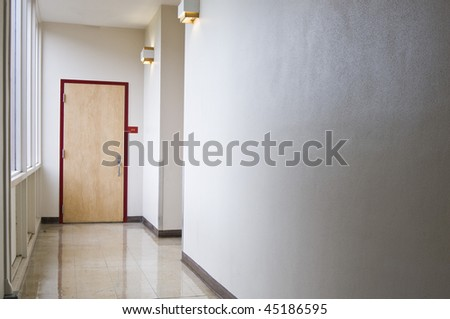 An empty hallway leading to a closed door. Windows let light into the hall coming from the left. - stock photo