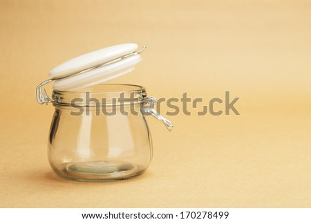 An empty jar with an open white lid on a background of a wrapping paper - stock photo