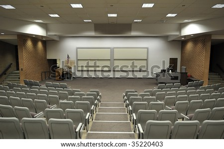 An empty lecture hall with a large amount of seats - stock photo