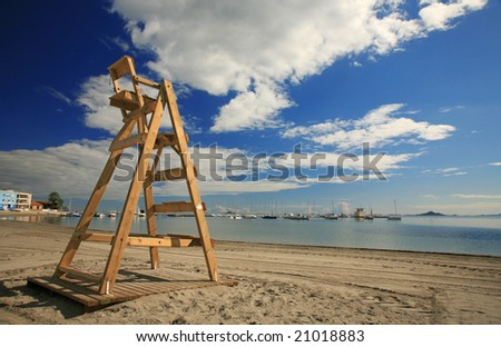 an empty lifeguard chair looking out to see in the late evening sunshine - stock photo