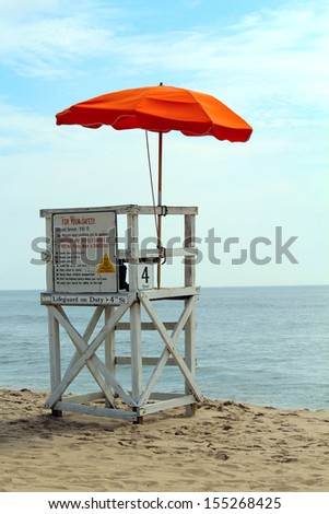 An empty lifeguard tower overlooking the ocean at the beach. - stock photo