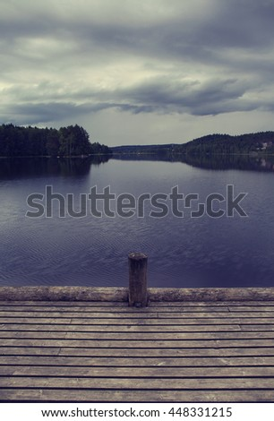 An empty pier before the storm. The storm is about to rise. Dramatic cloud formations above the lake. Image has a vintage effect applied. - stock photo
