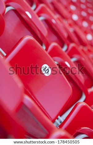 an empty red seat in stadium number 10 - stock photo