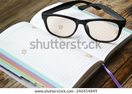 An empty retro daily planner with black pencil and reading glasses - stock photo