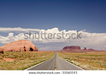 An empty road stretches into the distance through the American West.