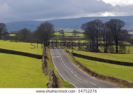 An empty road through the rolling fields of the English countryside - stock photo
