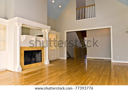 An empty room in a large modern house, with sunlight coming in the windows. - stock photo