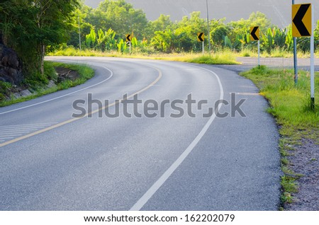 An empty S-Curved road with sign - stock photo