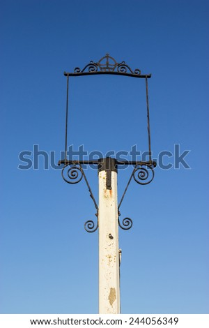 An empty sign, with scrolled metal work on a white post, previously a public-house sign. - stock photo
