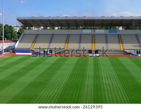 An empty soccer stadium with empty tribunes and grass brushed under blue sky - stock photo