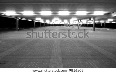 an empty spacious parking lot by night in black and white - stock photo