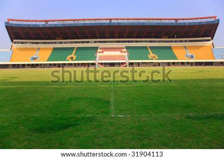 An empty  stadium with empty tribunes and grass brushed under blue sky in the southeast of China.