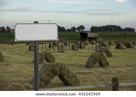 An empty street name tag in a rural area around sunset. On the background there are stacked hay bales, a little shed and a blue sky visible.  - stock photo