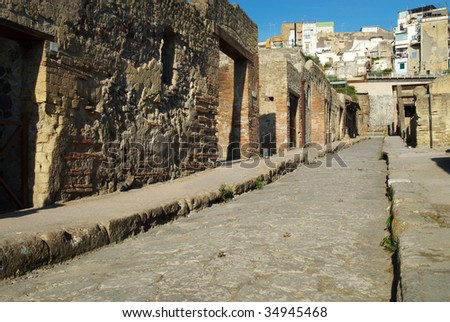 An empty street runs between the remains of ancient roman buildings, Herculaneum, Italy - stock photo