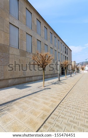 An empty street with a wall of a building and trees - stock photo