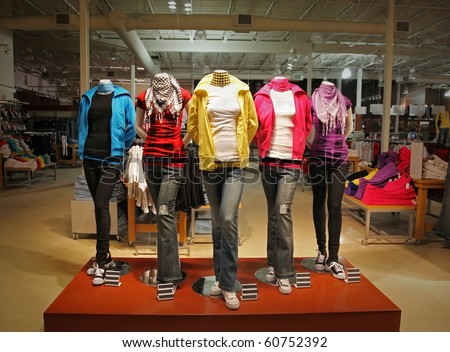 An empty teenage fashion store with five mannequin displaying the latest trend with jeans, hoodies, t-shirts and scarfs.