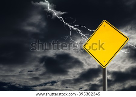 An empty traffic sign against a dark, cloudy and thunderous sky. Conceptually warning of danger ahead. Blank sign for copy space and message.