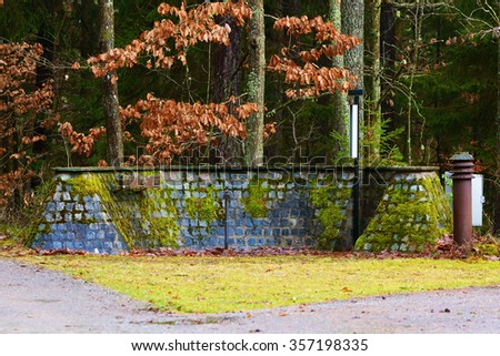 An empty water and vase service depot at a cemetery. Moss is covering the granite blocks of stone and the lamp to the right is rusty. Hangers are empty. Weather is damp and brown leaves hang on trees. - stock photo