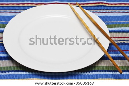 An empty white plate on a colorful placemat with a pair of chopsticks