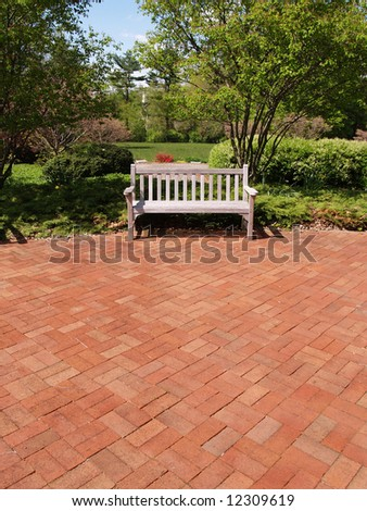 an empty wooden bench by a brick patio and garden - stock photo