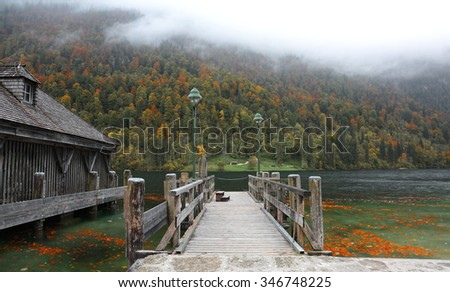 An empty wooden pier by beautiful lakeside on a misty foggy morning ~ Gloomy autumn scenery of Konigssee (King's lake) in Bavaria, Germany - stock photo