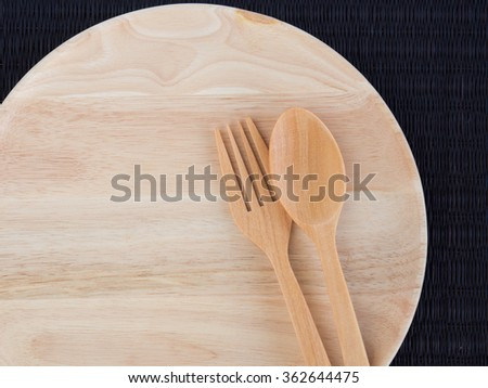 An empty wooden plate with wooden spoons and forks on black woven placemat - stock photo