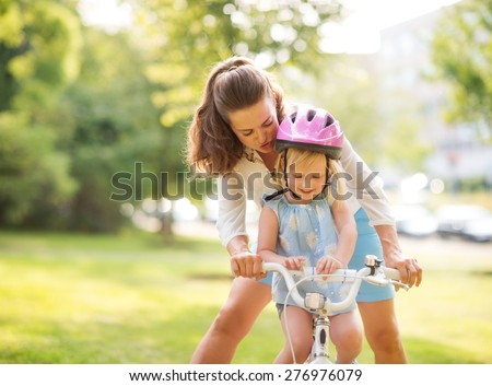 An encouraging mother helps her daughter learn how to steer her new bicycle. Wearing a pink helmet, the blonde daughter is proud and happy, looking down while smiling.  - stock photo