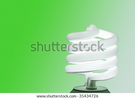 An energy-efficient CFL bulb illuminating a green background - stock photo
