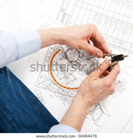 An engineer checking a technical drawing with a pair of compasses and a triangle