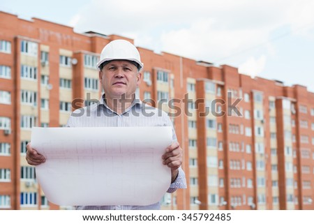 An engineer examining blueprints on a background with buildings - stock photo