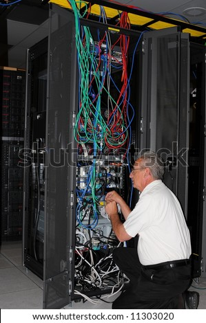 An engineer examining machine in computer room data center