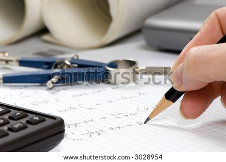 An engineer finishes up the calculations for a design - stock photo