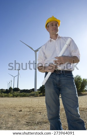 An engineer holds blueprints with wind turbines in the background. - stock photo