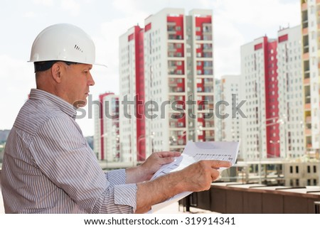 An engineer in white helmet examining blueprints on a background with buildings
