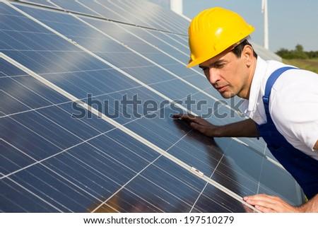 An engineer or installer inspecting solar energy panels - stock photo