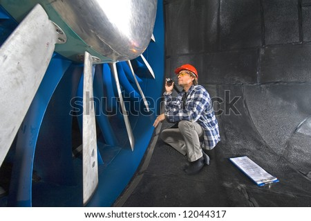An engineer, wearing a checkered shirt, inspecting the rotors of a huge industrial wind tunnel - stock photo