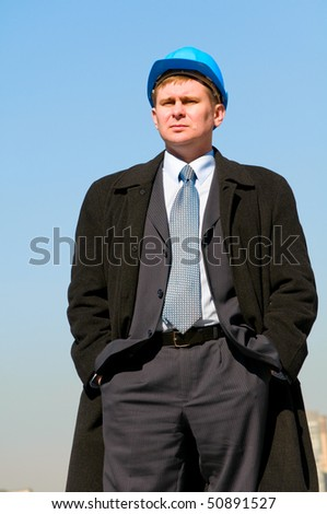 An engineer with blue hard hat standing confidently on sky background - stock photo