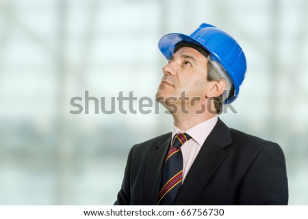 An engineer with blue hat looking up - stock photo
