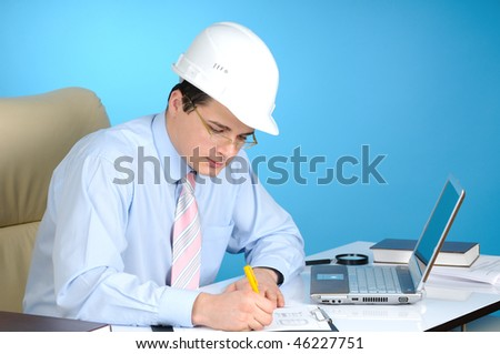 An engineer with white hard hat at work  on blue background - stock photo