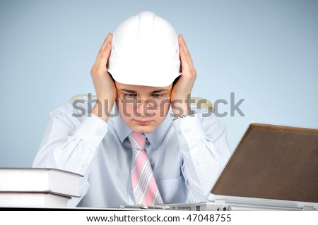 An engineer with white hard hat at work on gray background - stock photo