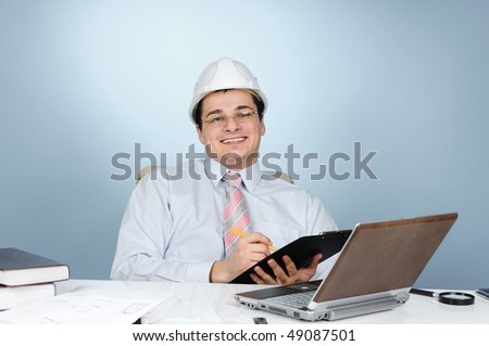 An engineer with white hard hat holding clipboard on gray background - stock photo