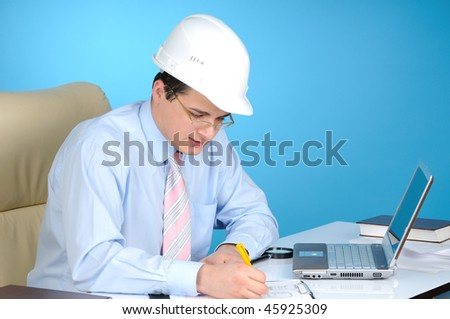 An engineer with white helmet at work  on blue background - stock photo