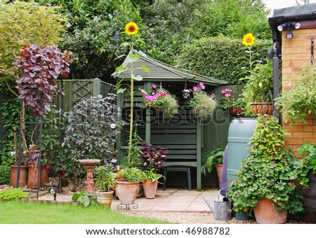 An English Back garden scene with Potted Plants and Gazebo - stock photo