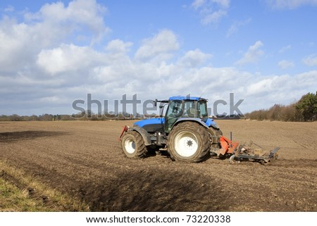 an english landscape with a blue tractor cultivating a field on a blustery spring day with a backdrop of trees and blue sky with clouds - stock photo