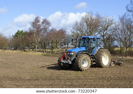 an english landscape with a blue tractor cultivating a field on a blustery spring day with a backdrop of trees and blue sky with clouds