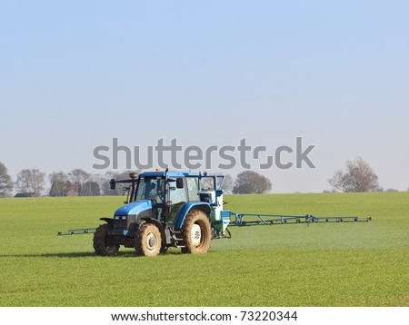 an english landscape with a blue tractor mounted sprayer working on a winter wheat crop on a fine day in february - stock photo
