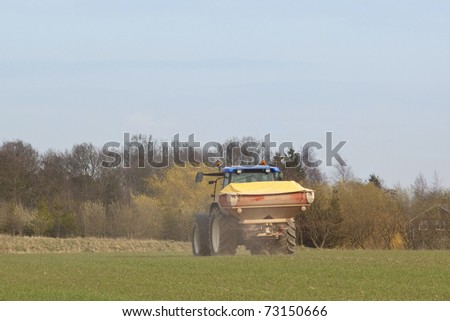 an english landscape with a tractor spreading fertilizer on a field under a blue sky - stock photo
