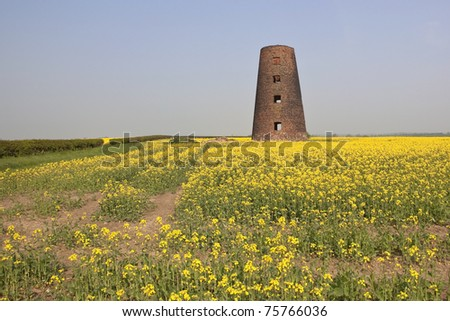an english landscape with an old windmill in farmland under a blue sky in springtime - stock photo