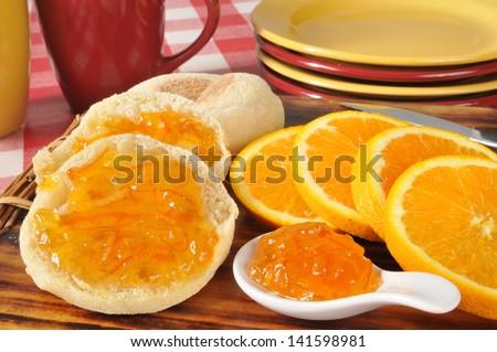 An English muffin with orange marmalade - stock photo